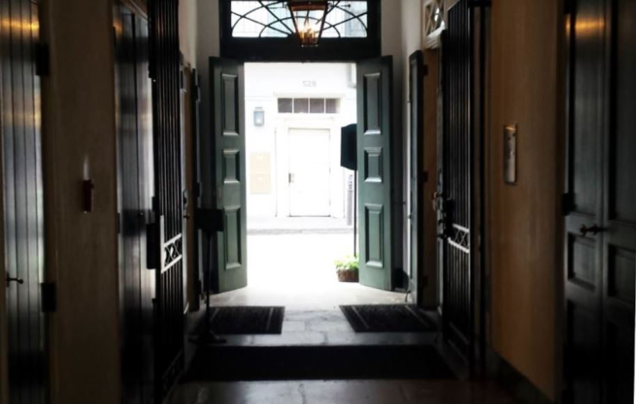 Looking out of dark hallway with doors in each side to two open doors with bright light illuminating the darkness.