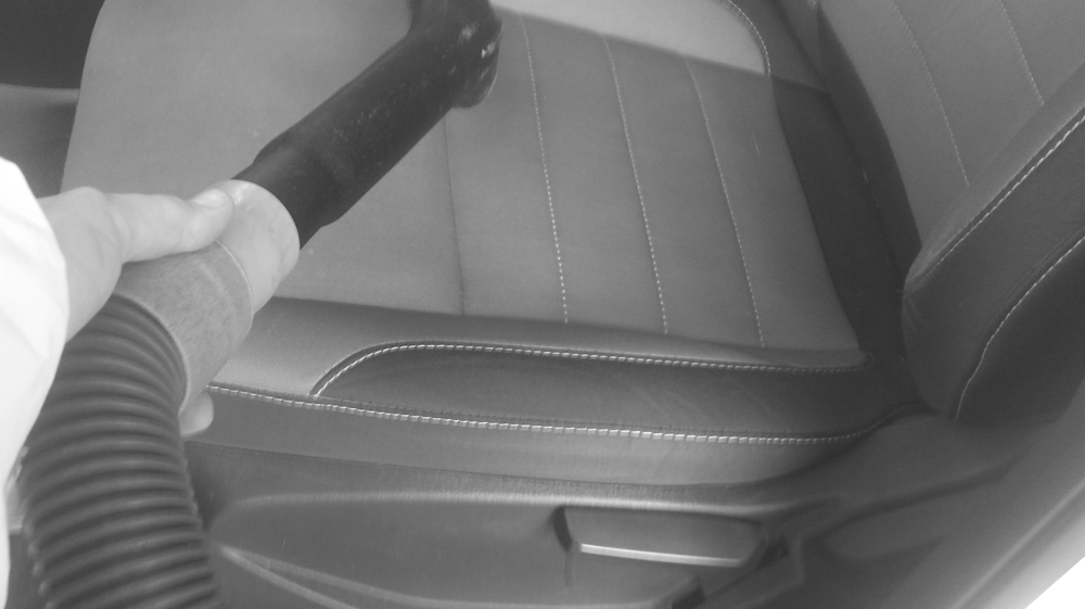 photo of a vacuum hose with a person vacumming a car seat.