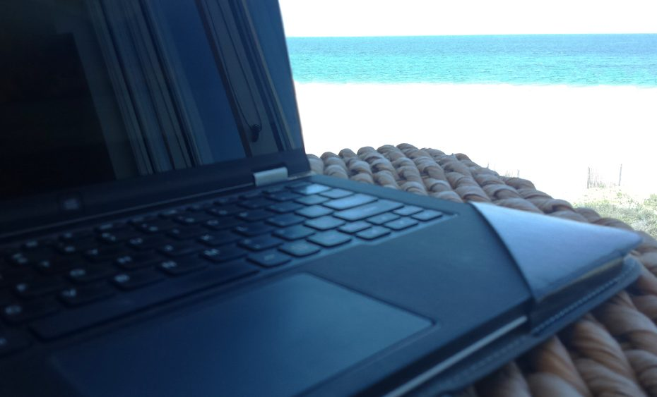 laptop sitting on a wicker table overlooking an ocean of emarld and sand of white.